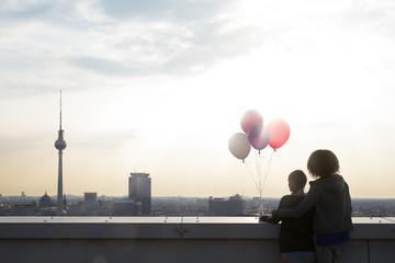 Deutschland, Berlin, Junge Frauen auf Dachterrasse, die Luftballons fliegen