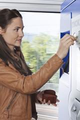 Frau am Fahrkartenautomaten im Zug