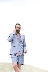 Deutschland, Bayern, Geschäftsmann spricht auf dem Handy und mit Tablet PC
