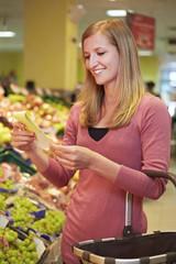 Deutschland, Köln, junge Frau mit Einkaufsliste im Supermarkt