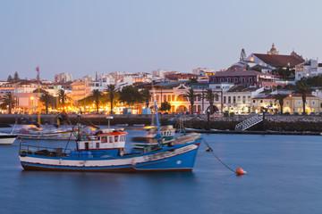 Portugal, Lagos, Blick auf Fischerboot im Hafen und Stadt im Hintergrund