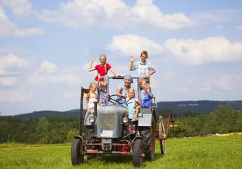 Deutschland, Bayern, Frau mit einer Gruppe von Kindern sitzt im alten Traktor