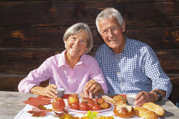 Deutschland, Bayern, Senior Paar Essen Almjause auf Berghütte