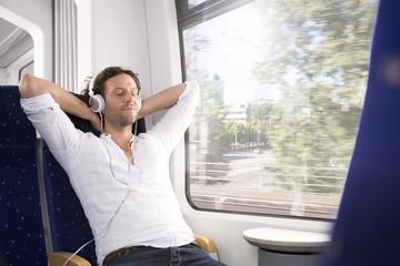 Mann mit Kopfhörern in einem Zug