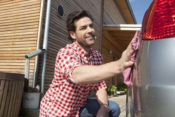 Deutschland, Nürnberg, mann wäscht Auto vor dem Haus