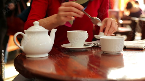 Woman hands sweetening coffee in cafe