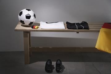 Fußball- Shirt, Hose und Schuhe auf Bank mit deutscher Flagge