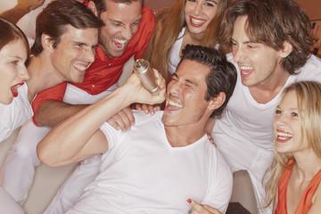 Deutschland, Stuttgart, Mann -Karaoke- Singen mit seinen Freunden im Nachtclub