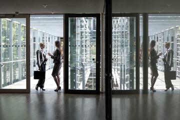 Zwei Geschäftsfrauen sprechen in Bürogebäude