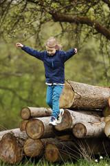 Deutschland, Baden Württemberg, Mädchen springt auf Holzstämmen