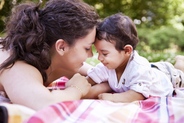 Mutter streichelt ihr Baby auf Decke