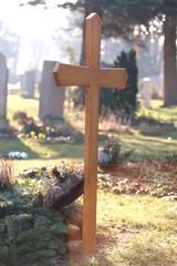 Holzkreuz auf Friedhof in Morgensonne