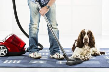 Mann Reinigung Teppich mit vaccuum Reiniger, während Hund sitzt