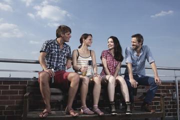 Deutschland, Berlin, Männer und Frauen auf der Dachterrasse sitzen