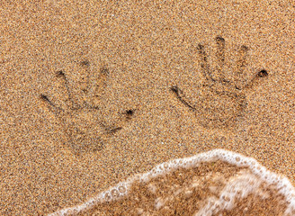 Handprint on sand being washed away