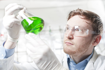 Deutschland, junger Wissenschaftler, der grüne Flüssigkeit in Erlenmeyerkolben