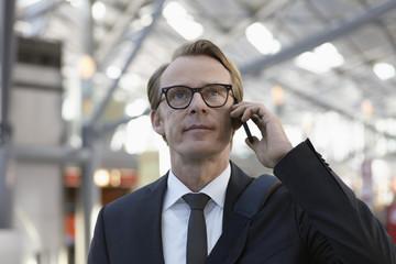 Deutschland, Köln, Mann am Telefon am Flughafen
