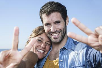Spanien, Paar mittleren Alters, das Friedenszeichen
