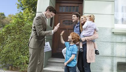 Deutschland, Düsseldorf, Immobilienmakler und Familie vor dem Haus