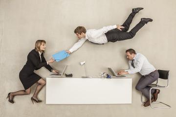 Geschäftsleute arbeiten, während ein anderer Geschäftsmann Bereitstellung Akte