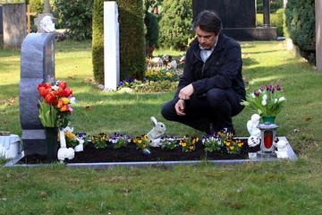 Mann trauert am Grab seiner Frau, Friedhof