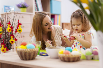 Mother and baby painting easter eggs