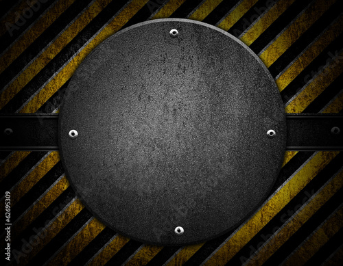 round metal plate on warning stripes background