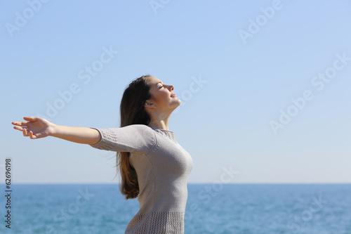 Happy woman breathing deep fresh air and raising arms - 62696198