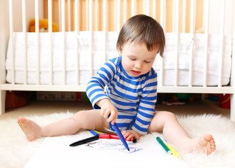 baby boy age of 18 months paints with pens