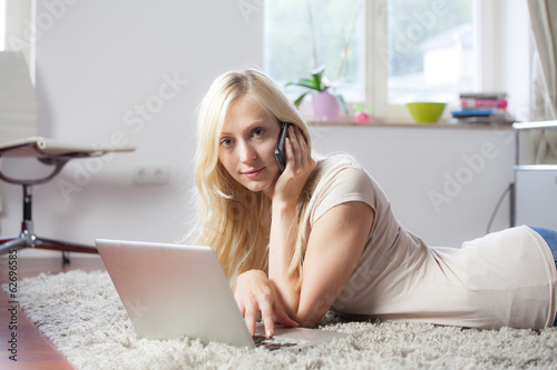 Woman using laptop and telephone on carpet