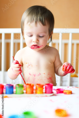 lovely baby with painting at home