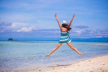 Young woman jumping and raising arms up on the beach
