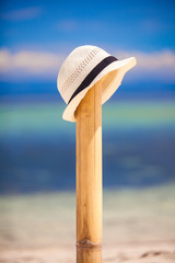 Straw hat on beach sand dune fence by turquoise ocean