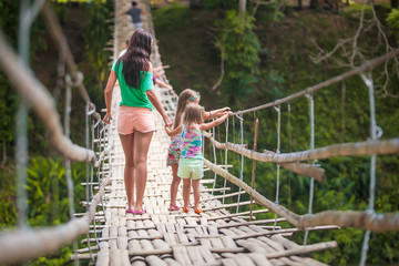 Back view of little girls and young woman walking on suspension