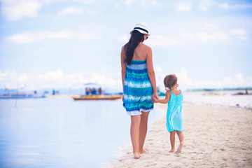 Back view of mother and her little daughter walking by the sea