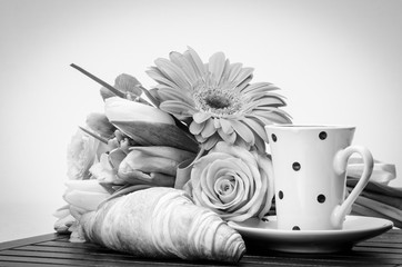 Croissant, cup with saucer and flowers