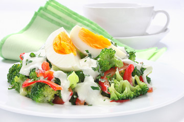 Salad with broccoli,  egg and sauce with yogurt and garlic