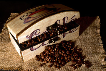 A wooden box filled with coffee beans on  jute table cloth