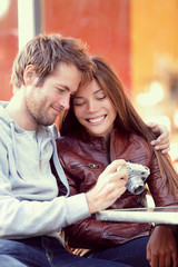 Happy young couple looking at pictures on camera