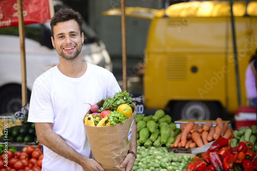 Man carrying a shopping paper bag full of fruits and vegetables.