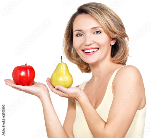 Young beautiful happy woman holds the apple and pear.