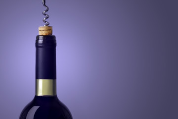 Opening a bottle of red wine, on blue background