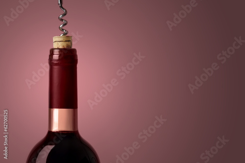 Opening a bottle of red wine, on purple background