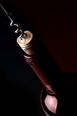Opening a bottle of wine, on dark background. Red reflection.