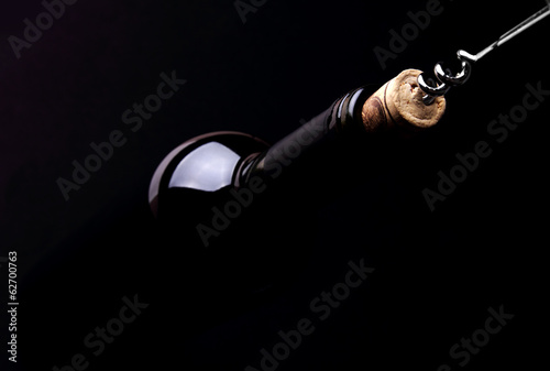 Opening a bottle of wine, on dark background - 62700763