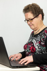 Elderly woman working at a laptop