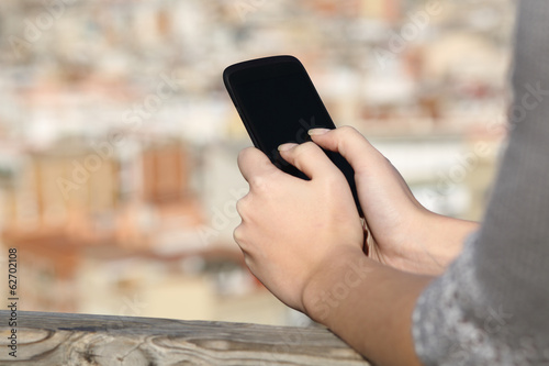 Woman hands texting on a smart phone with urban background