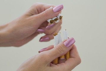 Quit smoking, human hands breaking up cigarette