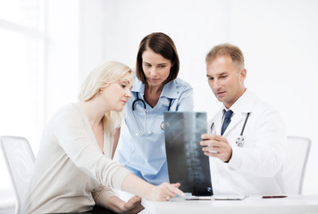 doctors with patient looking at x-ray