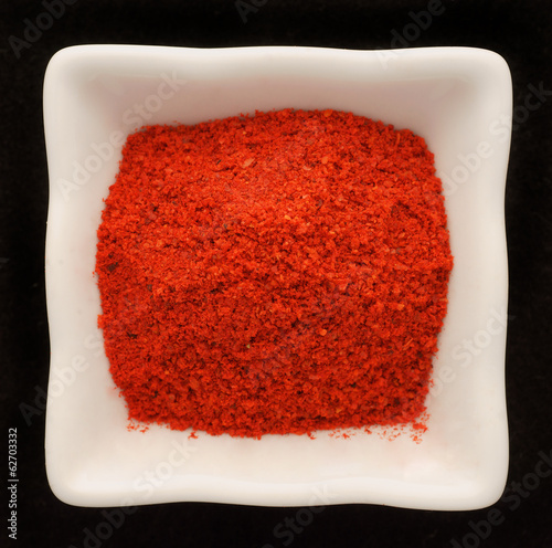 Spice pepper paprika in a ceramic bowl . Isolated on black.